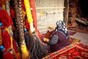 Woman weaving rug