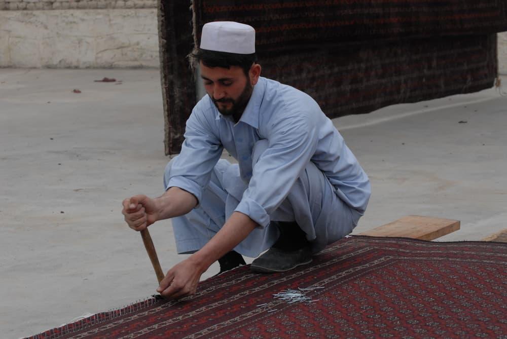 Man smoothing out carpet